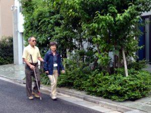 白杖を使っている男性が女性ガイドヘルパーと道路を歩いている写真