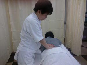 女性施術者がうつぶせの女性の腰に手をあてている写真