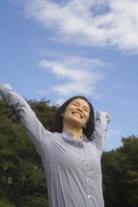 女性が青空の下、伸びをしている写真