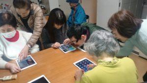 タブレット教室でアイパットを触りながら教わっている様子の写真